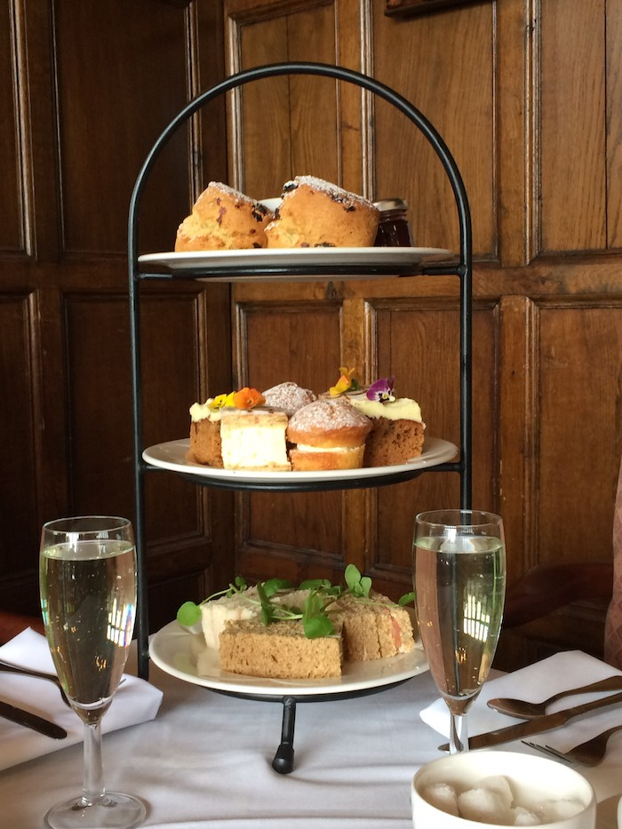 Afternoon tea feast with sandwiches, cakes, scones and Champagne.
