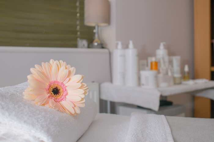 Pink flower on a spa treatment bed, with skin care products in the background.