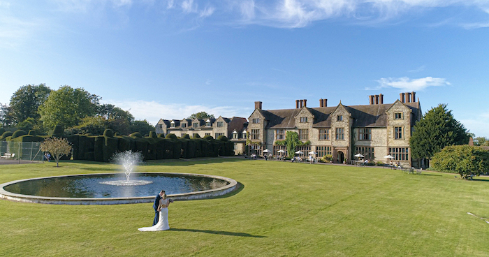Exterior of Billesley Manor, with bride and groom looking out into the landscape.