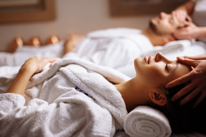 Two young people receiving head massages in a spa setting.