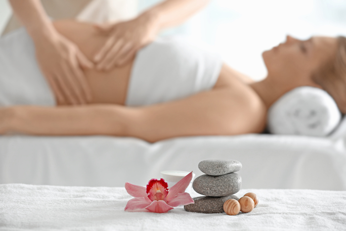 Pregnant lady having a massage in a spa, with massage stones in the foreground.