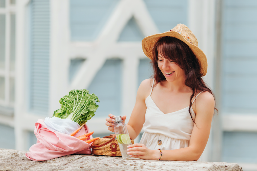 Plastic free tips: Woman sat with groceries and reusable water bottle