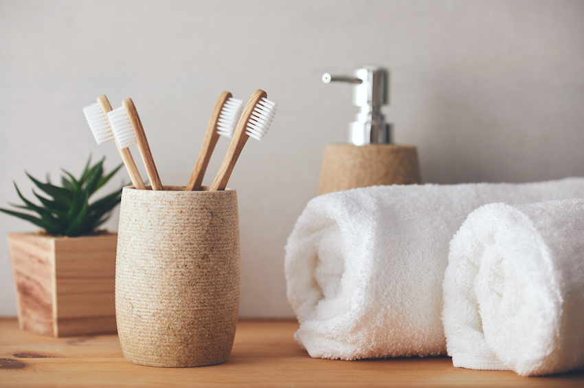 Plastic free tips: Bamboo toothbrushes with towels, plant and soap dispenser